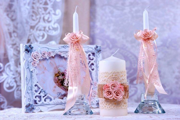 Белые свадебные свечи с розовой отделкой лентами и бутонами